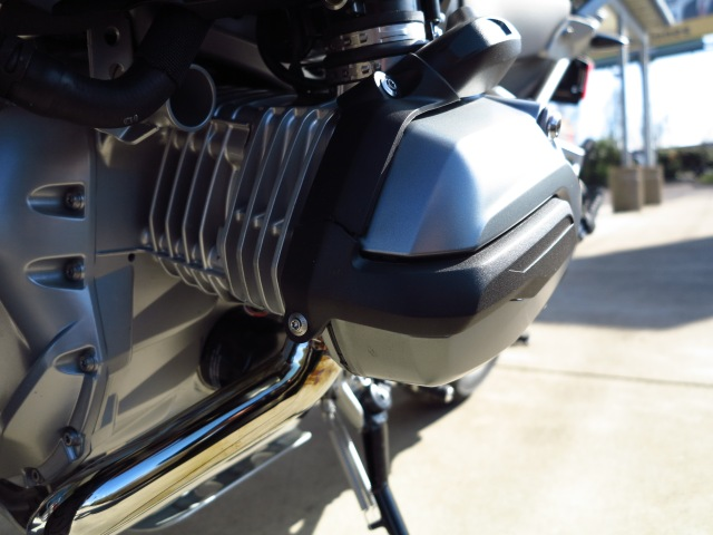 The boxer motor stays. Cylinder heads continue to be mostly air cooled. Intake moves to the top, exhaust at the bottom.