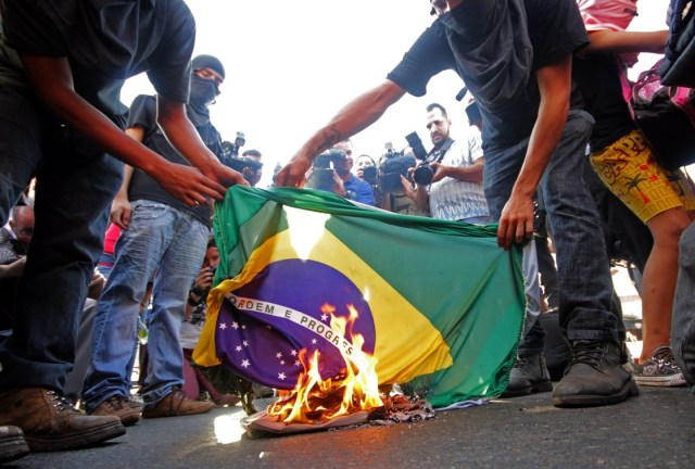 Brazilians demonstrate against the cup - burning the Brazilian Flag